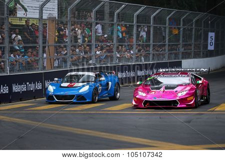 KUALA LUMPUR, MALAYSIA - AUGUST 08, 2015: Eric Wong (blue) races with Naoki Yokomizo (purple) at turn 2 of the city street circuit in the KL City GT CUP Race of the 2015 Kuala Lumpur City Grand Prix.