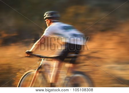a man riding a bicycle down a dirt trail in the back country to get away from the city toned with a retro vintage instagram filter app or action effect
