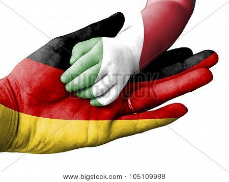 Adult Man Holding A Baby Hand With Germany And Italy Flags Overlaid. Isolated On White
