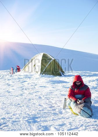 A Man Sits In A Sleeping Bag Near The Tent And Snowshoes.