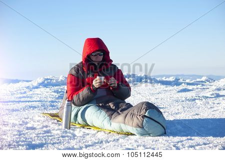 A Man Sits In A Sleeping Bag.
