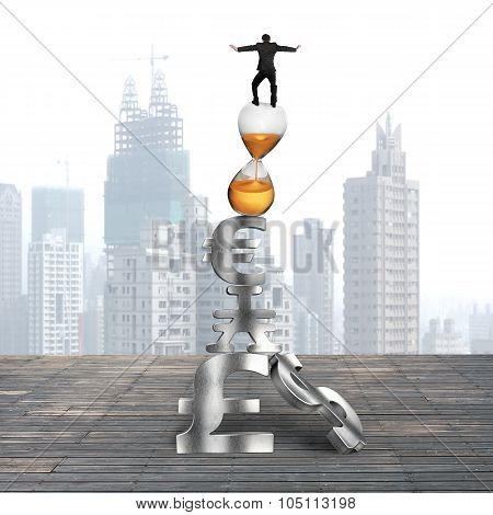Businessman Balancing On Hourglass And Currency Symbols