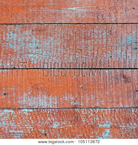 Weathered old wood texture with red flaked paint.