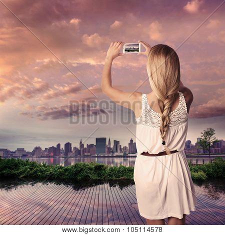 Blond tourist girl taking photo of Manhattan skyline in New York at sunset Photomount