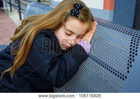 Blond kid girl pretending being sleep on a street bench
