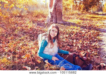 Autumn kid girl with pet dog relaxed in fall forest in Parc de Turia Valencia Spain