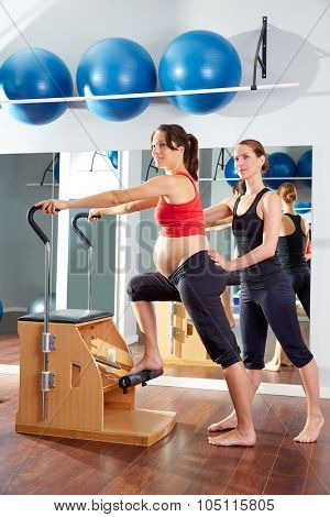 pregnant woman pilates exercise wunda chair at gym with personal trainer