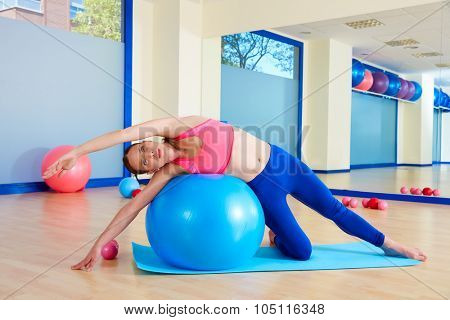 Pilates woman side bend fitball exercise workout at gym indoor swiss ball