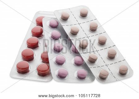 Set of colorful pills in a blister pack on white background