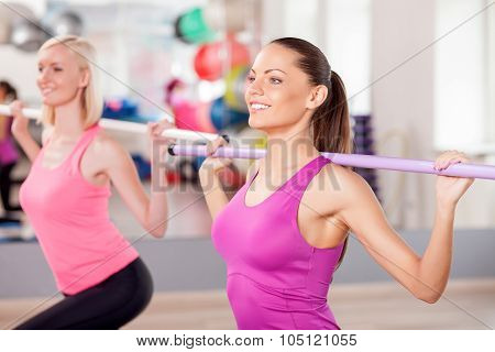 Cute fit women are exercising with equipment