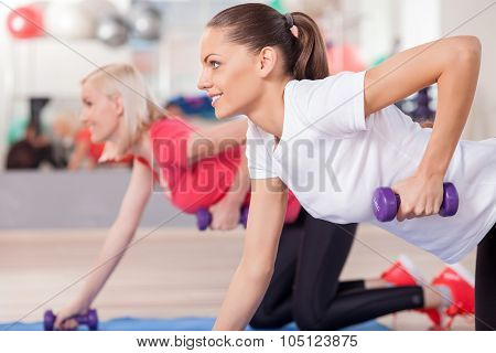 Attractive young women are training with weights