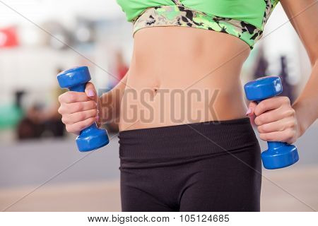 Cheerful young girl is exercising with weights