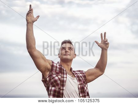 Successful sexy muscular man with hands raised