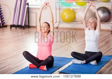 Pretty fit ladies are exercising in gym
