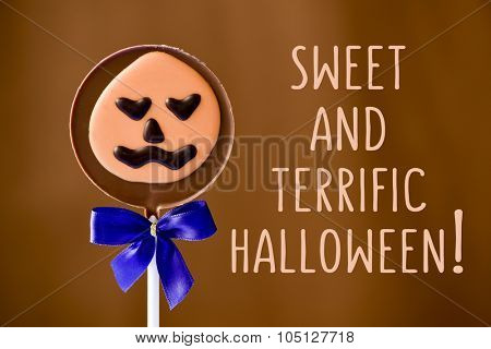 a pumpkin-shaped chocolate lollipop and the text sweet and terrific halloween against a brown background