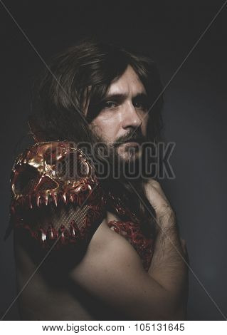 Theatrical, armored warrior king red skulls, long hair and intense look