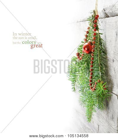 Fir Branches With Christmas Baubles Hanging As A Winter Decoration At A Wooden Wall Against White