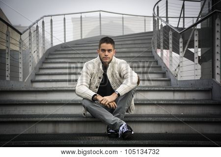 Young man in casual clothes sitting cross legged on stairway.