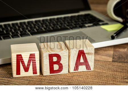 MBA written on a wooden cube in front of a laptop