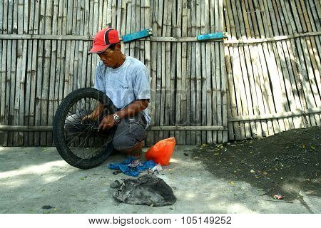 motorcycle mechanic fixing a motorcycle's tire