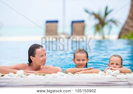Adorable girl and happy mom enjoying vacation in outdoor swimming pool