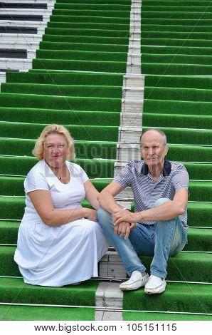 senior couple sitting on green carpet