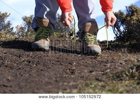 hiking woman hiker tying shoelace on beautiful mountain peak