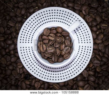 Cup Polka Dots Standing On Coffee Beans. Blur, Top View, Focus On Beans In Mug