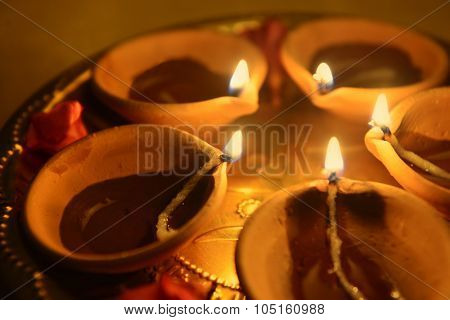 A colse up many earthen indian lamps in a brass plate.