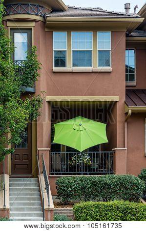 Green Umbrella On Stucco Patio