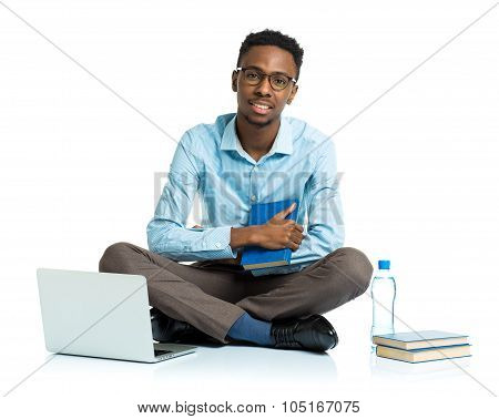 Happy African American College Student With Laptop, Books And Bottle Of Water Sitting On White