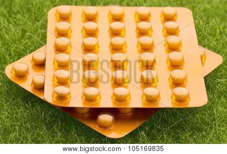Set of orange pill blister pack on grass background
