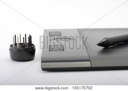 A Close-up Of  Pen On Graphic Tablet And Nibs On Stand