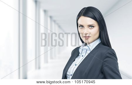 A Portrait Of Beautiful Brunette Professional In Formal Suit. Bright Modern Office In Blur On The Ba