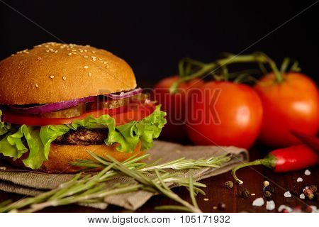 Beautiful juicy burger with cutlet of beef on wooden table.