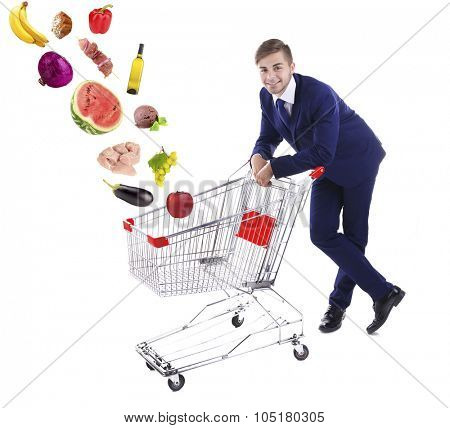 Young man pushing  shopping cart with different food, isolated on white