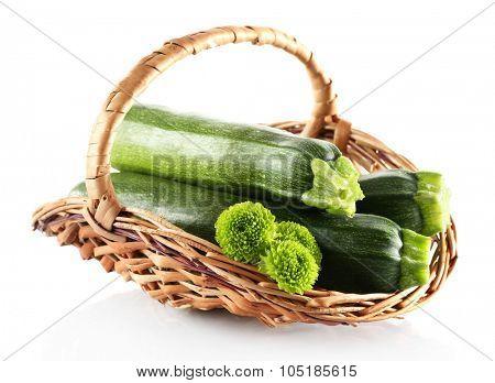 Fresh zucchini in wicker basket isolated on white