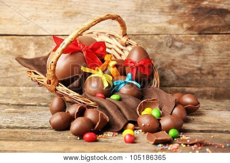 Chocolate Easter eggs in basket on wooden background