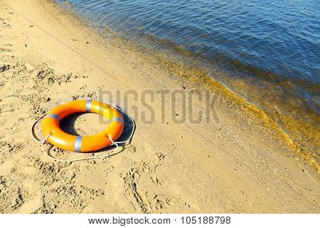 A life buoy on sandy beach