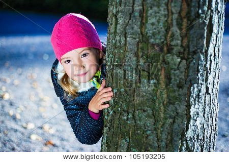 Portrait Of Little Girl Hiding Behind A Tree