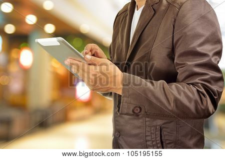 Young Man Hands Holding Tablet In Shopping Mall