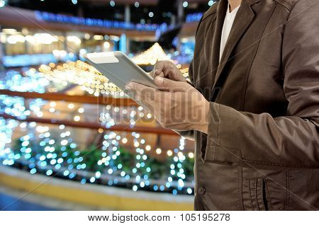 Young Man Hands Holding Tablet Or Mobile Device In Shopping Mall At Night.