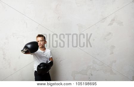 Little boxer fighter standing in boxing gloves and shows his jab