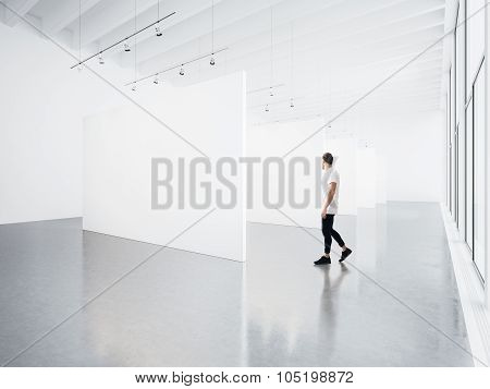 Gallery interior with white canvas and young man.
