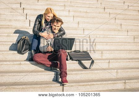 Couple Of Young Hipster People With Computer Laptop In Urban Location On Autumn Sunny Day