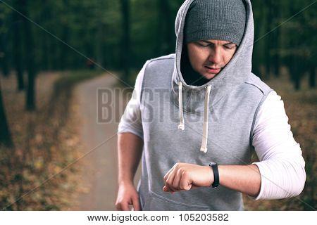Yong Man Using Fitness Bracelet During Morning Run