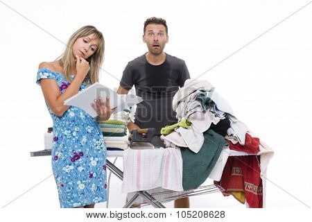 Woman Reading A Newspaper, While A Man Shocked And Sweating To Iron