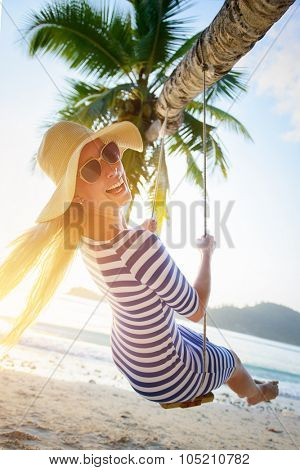 Young woman swinging at tropical beach smiling into the camera