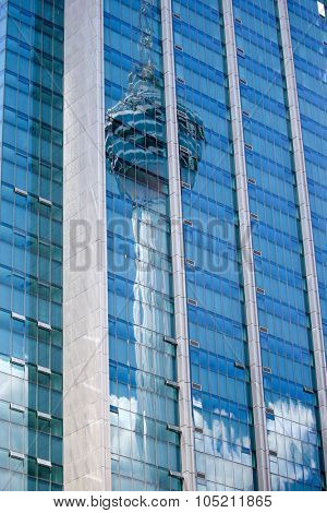 Reflection of the KL Tower, a telecommunication tower on a skyscraper's blue window panes facade on a day with blue skies in Kuala Lumpur city in Malaysia.