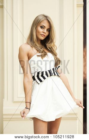 Romantic young blonde woman in white sexy dress, portrait on the background wall